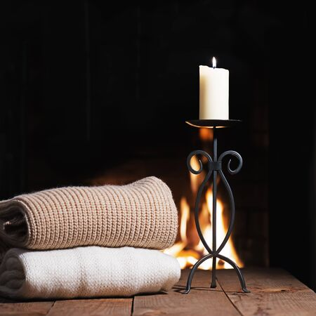 warm things: Warm woolen things and candle in candlestick near fireplace on wooden table. Winter and Christmas holiday concept.