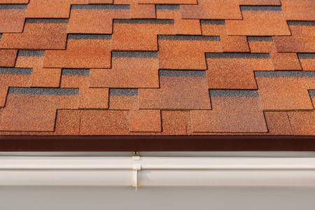 tejas: Betún tejas de asfalto con el drenaje de plástico en la azotea de la casa.