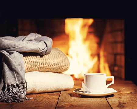 warm things: White cup of tea and warm woolen things near fireplace on wooden table. Winter and Christmas holiday concept. Photo with retro filter effect. Stock Photo