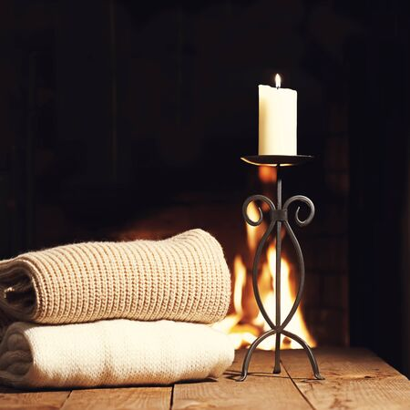 warm things: Warm woolen things and candle in candlestick near fireplace on wooden table. Winter and Christmas holiday concept. Photo with retro filter effect.