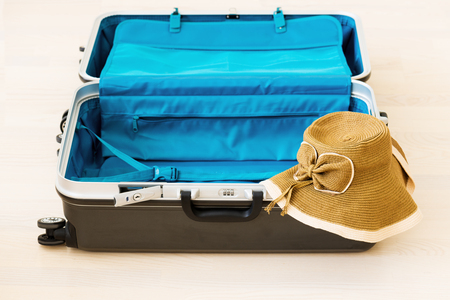 polycarbonate: Large family polycarbonate luggage and summer sunny wicker hat on white wooden background.