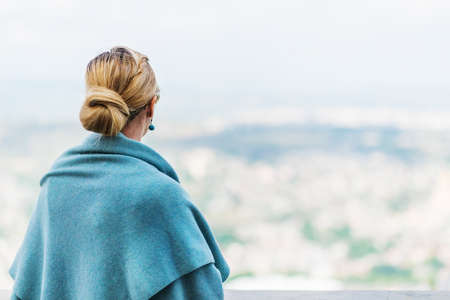 Back view of a woman with tied blond hair looking at the nature background during a nice sunny morning.