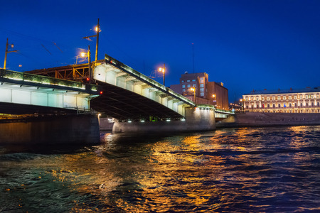 familiar: Night view of illuminated drawbridge (Foundry Bridge) on night river Neva water, one of the most familiar images of the Northern capital of Russia, Saint Petersburg. Stock Photo