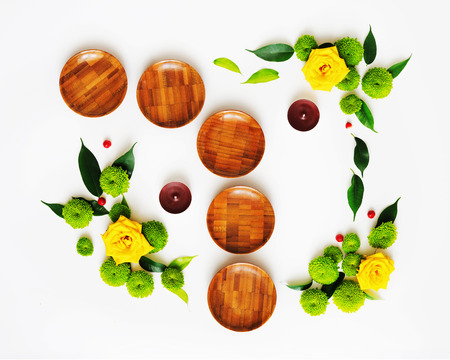 Wooden dishes with wreath frame from roses and chrysanthemum flowers, ficus leaves and ripe rowan on white background. Overhead view. Flat lay.