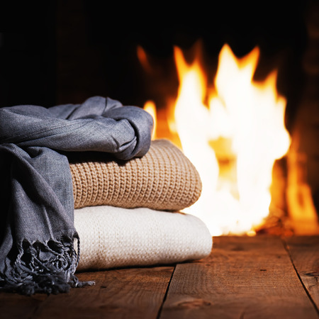 warm things: Warm woolen things near fireplace on wooden table. Winter and Christmas holiday concept.