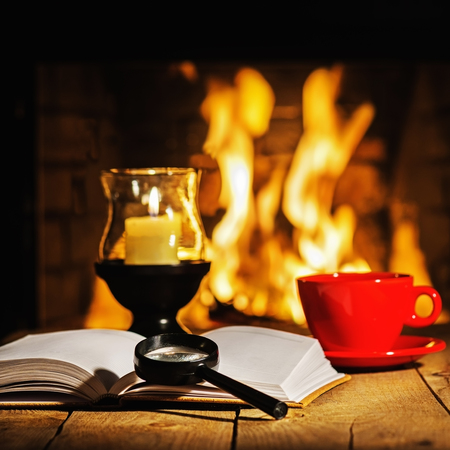 tea lamp: Red cup of coffee or tea, candle in lamp, magnifier glass and old book on wooden table near fireplace. Stock Photo