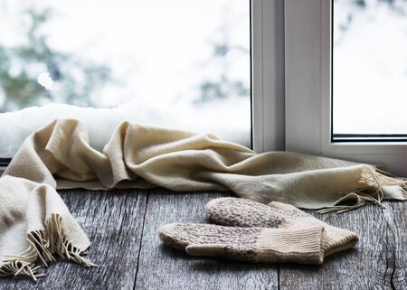 Beige woolen scarf and mittens located on stylized wooden window sill. Stok Fotoğraf