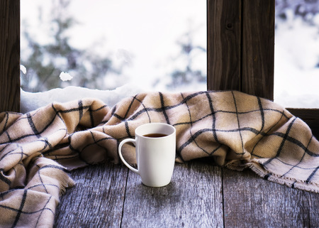 sill: White cup of coffee or tea and woolen plaid located on stylized wooden window sill. Stock Photo