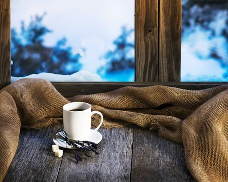 wooden window: White cup of coffee or tea, lavender flowers and natural gunny cloth located on stylized wooden window sill. Stock Photo