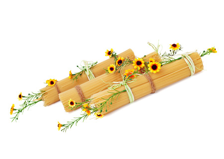 Uncooked Italian spaghetti decorated with yellow flowers isolated on white background. Stock Photo
