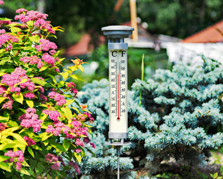 Modern stylish outdoor thermometer in summer garden. Closeup.