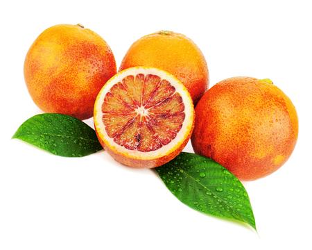Dojrzałe czerwone krwine pomarańcze z cięte i zielone liście na białym tle. Closeup. Zdjęcie Seryjne