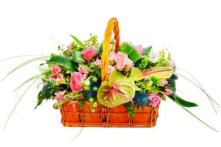 Flower bouquet arrangement centerpiece in a wicker gift basket isolated on white background.