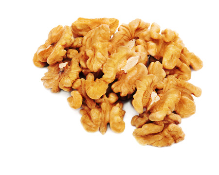 Heap of fresh shelled walnuts on white background. Close-up.