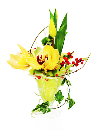 Bouquet from orchids, tulips and ivy arrangement centerpiece in glass vase isolated on white background.