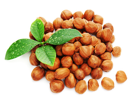 Heap of fresh shelled hazelnuts with green leaves isolated on white background. Closeup.