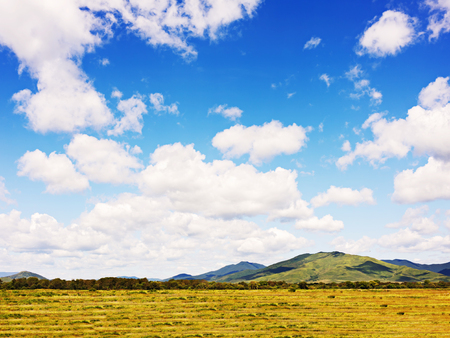 arable land: Landscape with mountain views, arable land, blue sky and beautiful clouds. Real scene without any light effects. Stock Photo