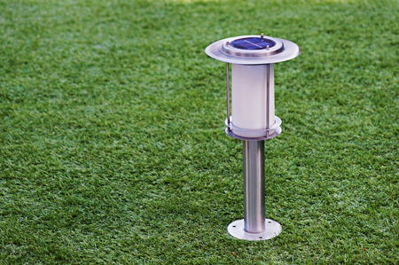 photocell: Solar-powered lamp on green grass background. Selective focus. Stock Photo