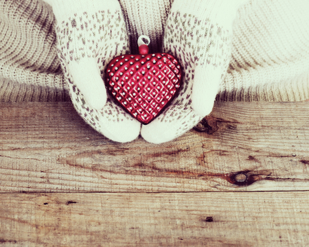 Woman hands in light teal knitted mittens are holding heart on wooden background. Winter and Christmas concept.