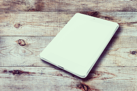 blank tablet: Tablet computer with blank screen on wooden background.