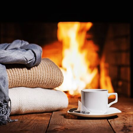 warm things: White cup of tea and warm woolen things near fireplace on wooden table. Winter and Christmas holiday concept. Stock Photo