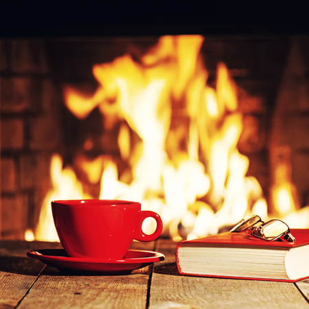 tea filter: Red cup of tea or coffee, glasses and old book near fireplace on wooden table. Winter and Christmas holiday concept. Photo with retro filter effect.