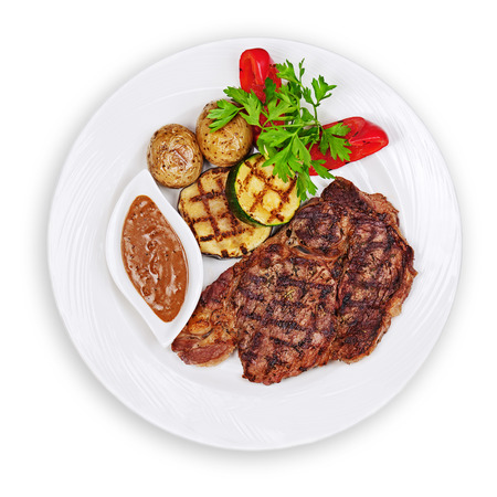 medium: Grilled steak, baked potatoes and vegetables on white plate isolated on white background. Stock Photo