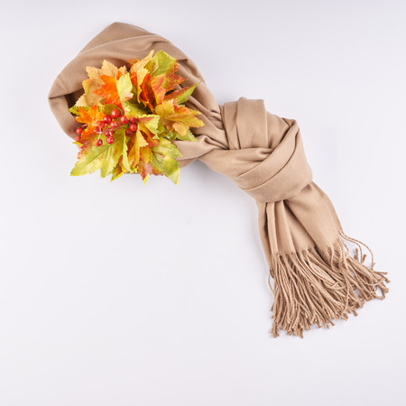 Scarf is tied in beautiful knot and autumn leaves on white background. Flat lay, top view with copy space.