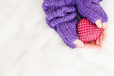 Woman hands in light teal knitted mittens are holding heart on snow background. Winter and Christmas concept.