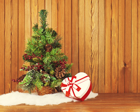 Christmas composition from pine tree, gift and decorations on wooden background with place for your wording. Stock Photo