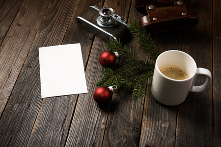 Old photos, camera, pine tree branch and cup of coffee with christmas decorations on wooden background.