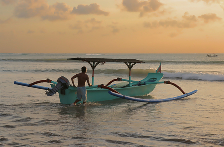 A traditional Balinese Outrigger Used as a Surfing tour boat pushed back out to sea at Sunset from Kuta Beach, Bali, Indonesia Stock Photo