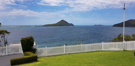 A view over nelsons bay from the garden of the lighthouse. looks out over a white picket fence towards boondelbah island.