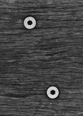 A black and white wood grain texture with 2 hex head screws in a minimalist style