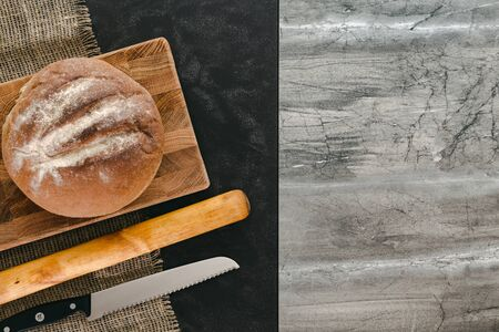 Bread on wooden board, black and grey marble background, top view.