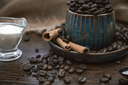 a blue ceramic cup full of coffee beans with cinnamon sticks, scattered coffee beans, milk and canvas fabric on brown wooden table Stock Photo