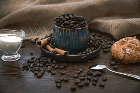 a blue ceramic cup full of coffee beans, with cinnamon sticks and spoon, scattered coffee beans, bun, milk and canvas fabric on brown wooden table
