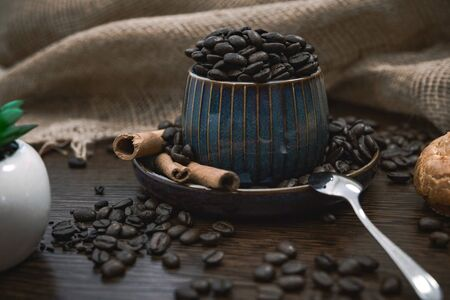 a blue ceramic cup full of coffee beans, with cinnamon sticks and spoon, scattered coffee beans, plant, bun and canvas fabric on brown wooden table