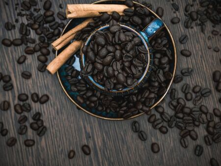 a blue ceramic cup with coffee beans and cinnamon sticks and scattered coffee beans on brown wooden table