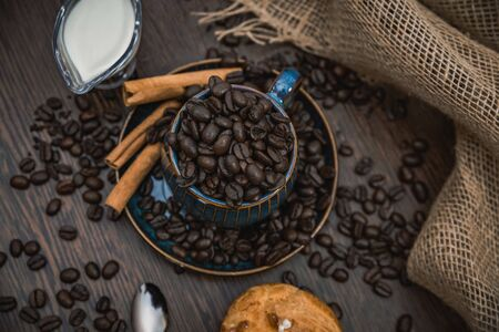 a blue ceramic cup full of coffee beans with cinnamon sticks, spoon, scattered coffee beans, bun, milk and canvas fabric on brown wooden table top view Stock Photo
