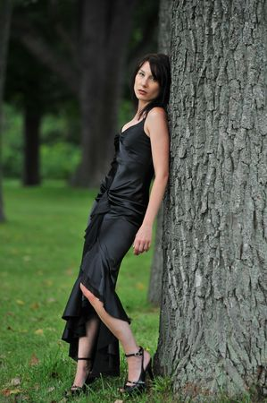 dark haired model posing outside by tree Stock Photo
