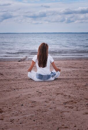 woman meditating on beach with seagull walking past Stock Photo