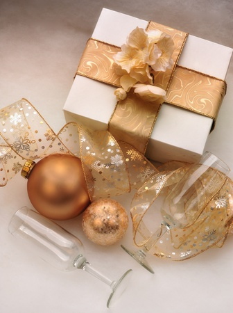 White box wrapped in a gold bow with champagne glasses and gold ornaments and ribbon Stock Photo