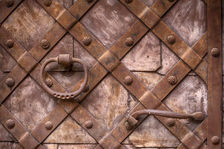 Fragment of the old iron door. Forged handle on the background of metal doors Stock Photo
