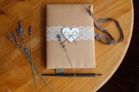 Vintage diary with handmade cover, textile heart, dry herbal grass on wooden table. Stok Fotoğraf