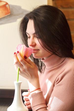 Beautiful brunette woman sniffing tulip