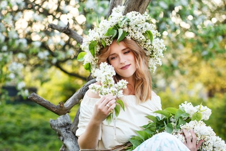 Portrait of young woman in lilac wreath. Young pretty girl holding flowers in their hands.