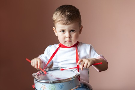 Little boy playing the drum. Lovely baby boy. Child development concept.