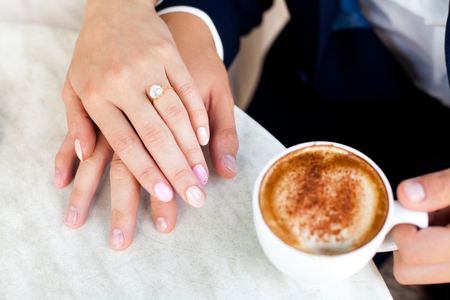 Wedding couple holding hands. Close-up. cup of coffee