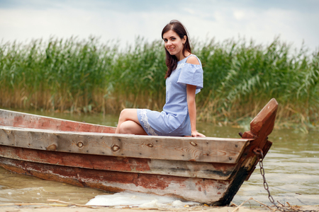 Pretty woman in an Old Wooden fishing boat. Beautiful woman smiling while sitting in a boat Stock Photo